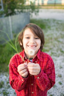 Child with dandelion in outside