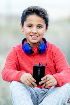 Child with dark hair listening music with blue hadphones and a mobile