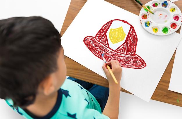 Bambino con un disegno del casco del pompiere
