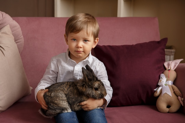 Child with easter bunny or rabbit at easter day