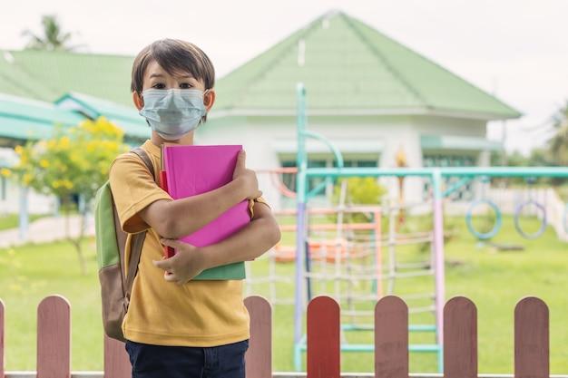 코비드-19 검역 및 폐쇄 후 학교에서 얼굴 마스크를 쓴 아이.