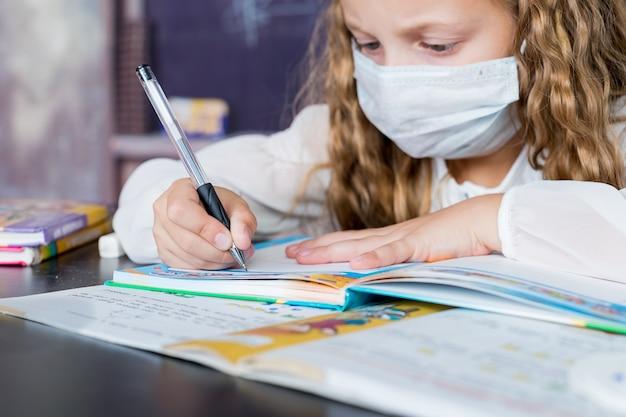 Covid-19の検疫とロックダウンの後、学校に戻ってフェイスマスクを持つ子供。本に書いて顔の防護マスクを持つ若い小学生少女。ペンに焦点を当てます。教育のコンセプトです。