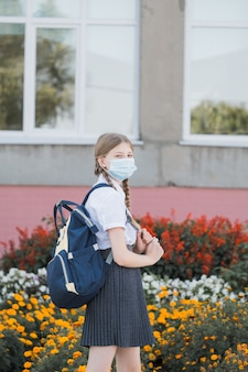 Child with face mask going back to school after covid-19 quarantine and lockdown. back to school university student girl wearing covid mask walking on campus with backpack, books and laptop