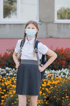 Ребенок в маске возвращается в школу после карантина и изоляции от covid-19. снова в школу студентка университета в маске covid гуляет по кампусу с рюкзаком, книгами и ноутбуком