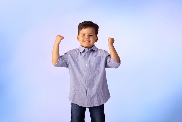 Child with facial expressions in a studio photo over colored background.
