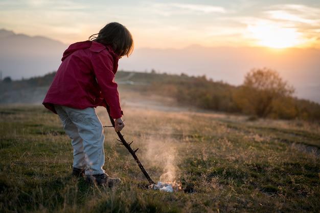 自然の中で火を持つ子供