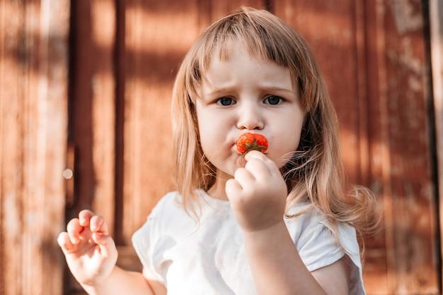 食べ物を持つ子供。いちごを健康的に食べる。