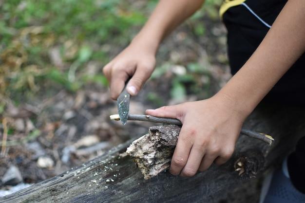 Ребенок с навыками выживания в лесу. молодой турист-путешественник с ножом