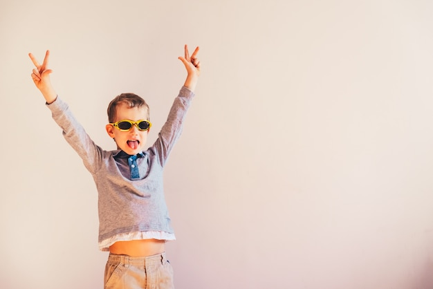 Child with funny sunglasses raising arms excited in victory sign.