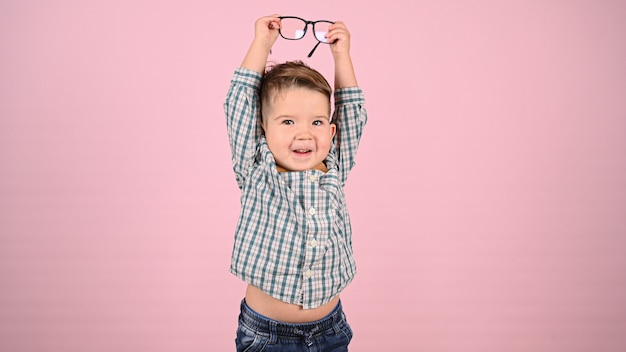Ребенок в очках, на розовом фоне. фото высокого качества