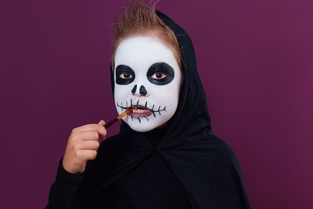 Child with halloween makeup in skeleton costume eats halloween jelly worms on dark purple background.