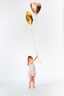 Child with heart-shaped balloons and stars