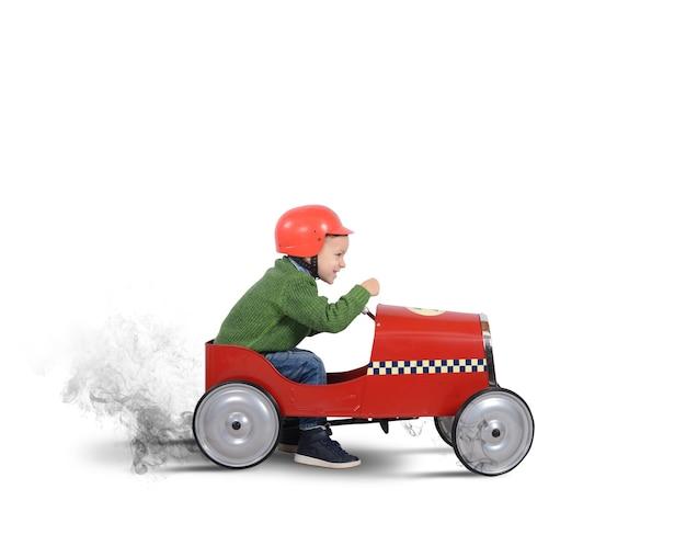 ヘルメットをかぶった子供が車で遊ぶ