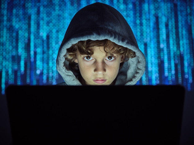 Child with a hood in front of a computer, staring and with binary code