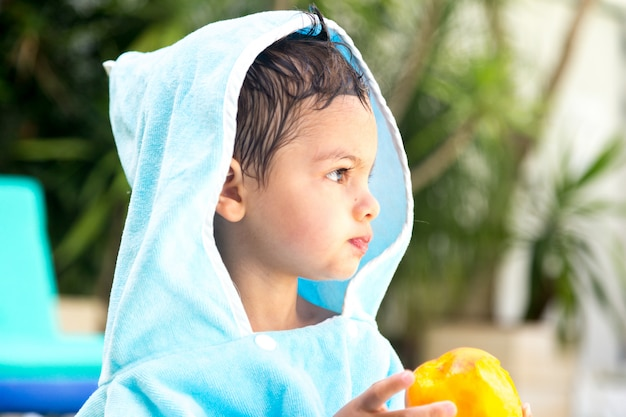 Child with a hooded towel facing forward while eating fruit