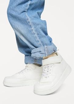 ジーンズの白いスニーカーを持つ子供