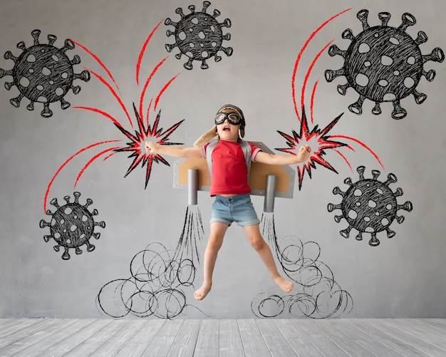 Child with jetpack jumping against grey concrete background. coronavirus covid-19 pandemic concept