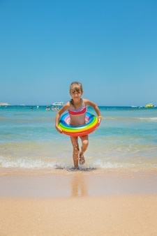 Child with a life buoy at sea