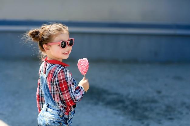 Ребенок с леденцом на палочке в руках на фоне стены