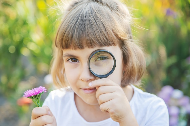 Child with a magnifying glass in her hands.
