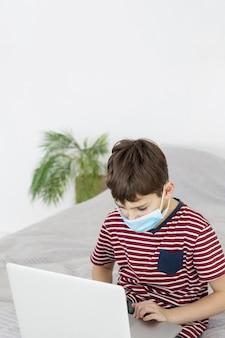 ノートパソコンを見て医療マスクを持つ子供