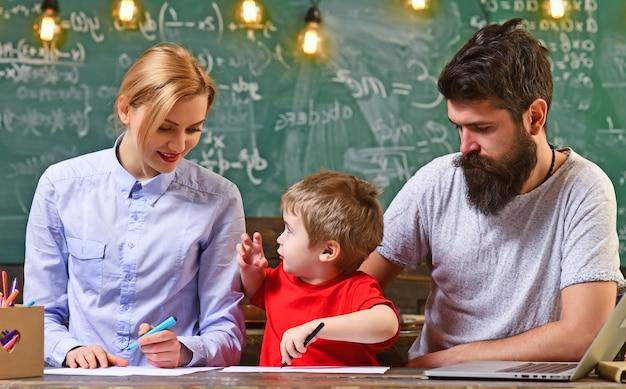 학교에서 어머니와 아버지와 아이입니다. 부모와 함께 작은 아이 연구. 가족 그림을 함께 즐기십시오. 창의력과 발달 어린이