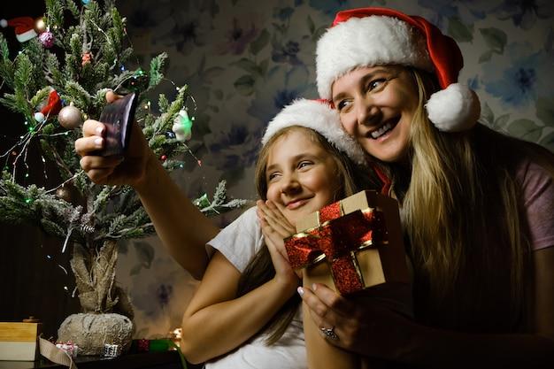 サンタの帽子をかぶった母親と子供がクリスマスの日にビデオ通話をし、自宅のクリスマスツリーのあるリビングルームのソファに座っている