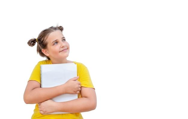 白い背景で隔離のノートを持つ子供。見上げる少女