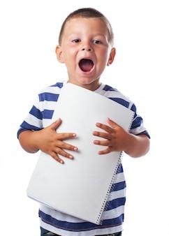 Bambino con la bocca aperta e blocco note in bianco