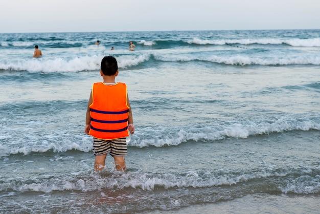 立って、海に見えるオレンジ色のライフジャケットを持つ子供