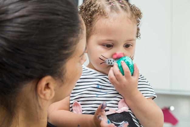 ペイントされたイースターバニーの顔と手に卵を持つ子供。