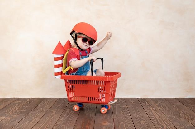 Ребенок с бумажной ракетой играет в помещении