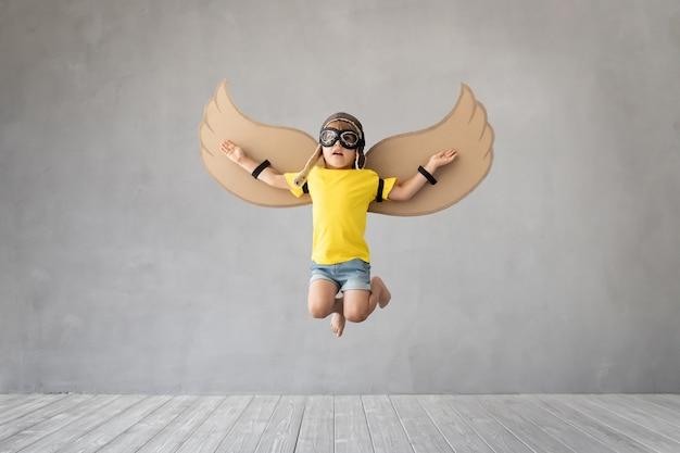 灰色のコンクリートの壁にジャンプする紙の翼を持つ子供。