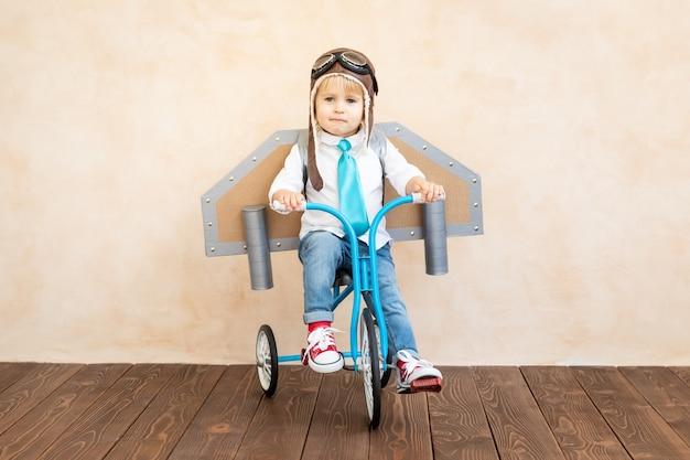 Ребенок с бумажными крыльями играет в помещении