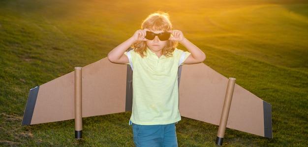 파일럿 안경을 쓴 아이가 여름 공원에서 장난감 비행기 날개를 가지고 놀고 있습니다. 혁신 기술과 성공 개념입니다. 공원에서 잔디에 재미 아이 파일럿.