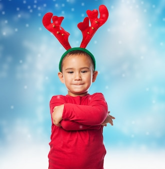 Child with plush reindeer antlers in snow background
