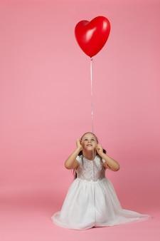 Ребенок с хвостиками в белом платье сидит на полу и смотрит на красный воздушный шар в форме сердца