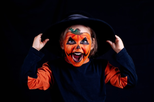 A child with pumpkin makeup in a black hat holds his hands to the hat and laughs loudly on a black wall, isolated,