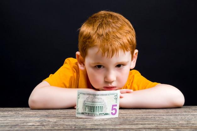빨간 머리를 가진 아이, 미국 달러와 함께 아름다운 소년의 클로즈 업 초상화, 작은 아이가 사용할 수있는 현금