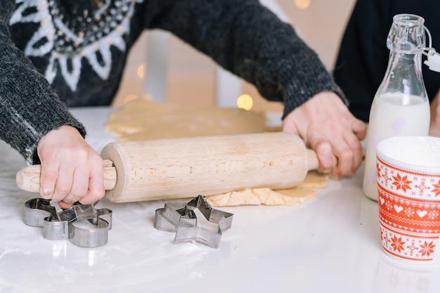Ребенок с скалкой выпечки печенья.