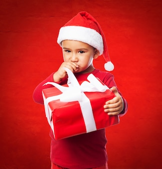 Child with santa cap touching his mouth
