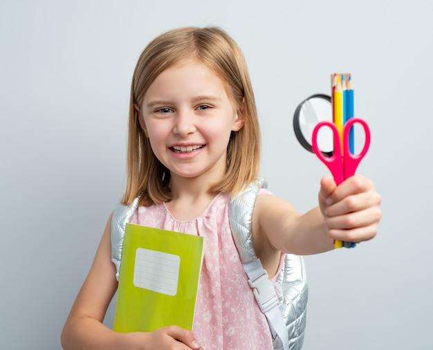 学用品とバックパックを持つ子供