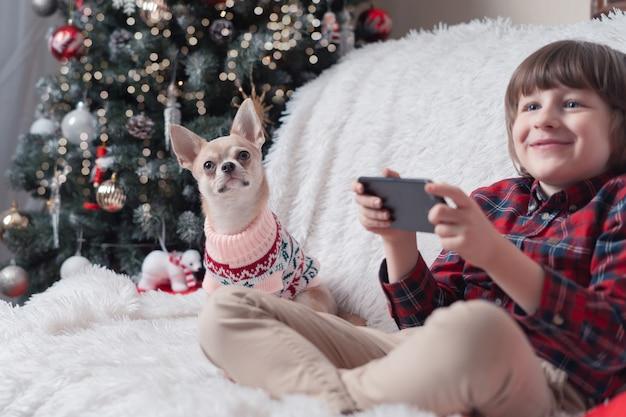 クリスマスにスマートフォンと彼の子犬を持つ子供。