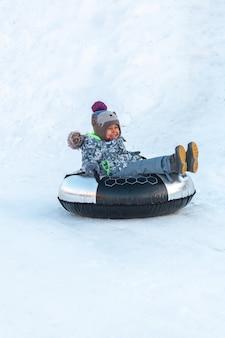 Ребенок с зимними занятиями сноутюбинг, спуск со снежного холма