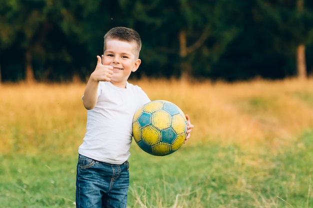 Child with soccer ball shows ok, at house garden with grass background, smiling