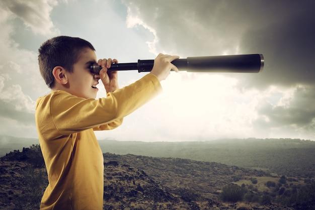 Ребенок в подзорной трубе далеко ищет новое приключение
