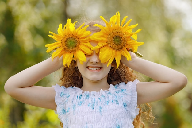 Child with sunflowers in his hand show white teeth; enjoying nature in summer sunny day.