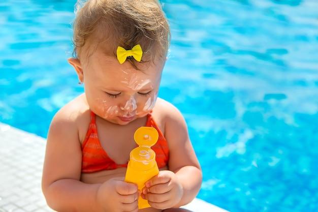 彼女の顔に日焼け止めを持っている子供。セレクティブフォーカス。