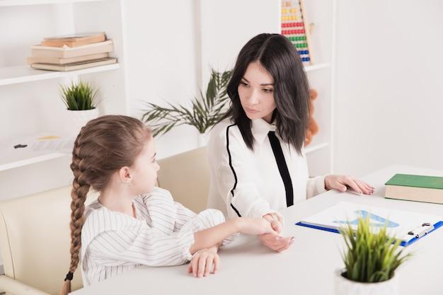 치료사와 함께 수업에 함께 앉아 발음과 소리를 연구하는 아이.