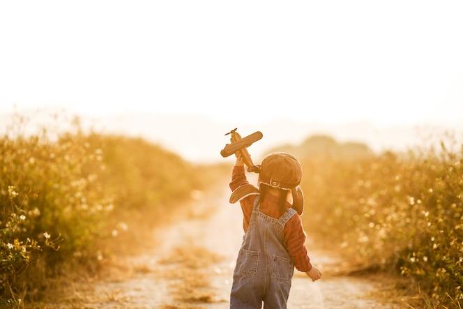 해질녘 자연 장난감 비행기와 아이